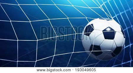 Soccer ball in goal on blue background