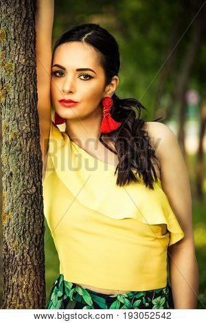 attractive dark hair woman portrait by the tree latino look with red lipstick and red striking earrings wearing yellow asymmetrical summer shirt