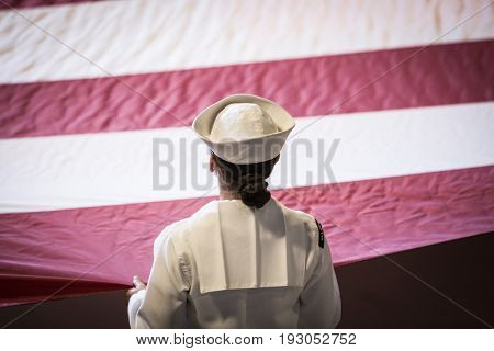 U.S. Navy military service member holds a large American Flag during the Memorial Day Observance ceremony on the Intrepid Sea, Air & Space Museum, Fleet Week, NEW YORK MAY 29 2017.