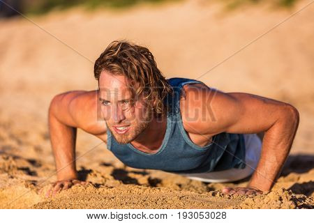 Push-up fitness man training pushups on beach doing bodyweight exercises for arms workout. Healthy lifestyle person working out muscles.