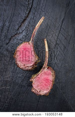 Barbecue Rack of Venison as top view on an old burnt wooden board