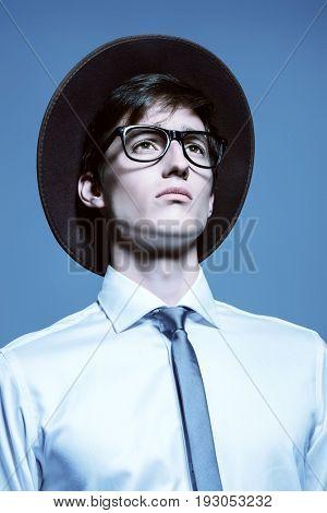 Fashion shot. Portrait of a purposeful young man posing in white shirt and a hat. Studio shot.