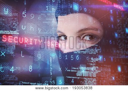 Portrait of female hacker wearing balaclava against abstract black room