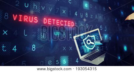 Hacker using laptop and debit card against abstract black room