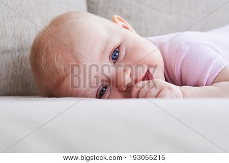 Close-up of pretty toddler lying on sofa and sucking thumb