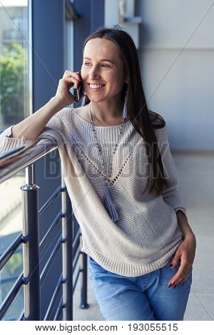Vertical of stylish brunet talking on phone while looking out window and leaning on handrail