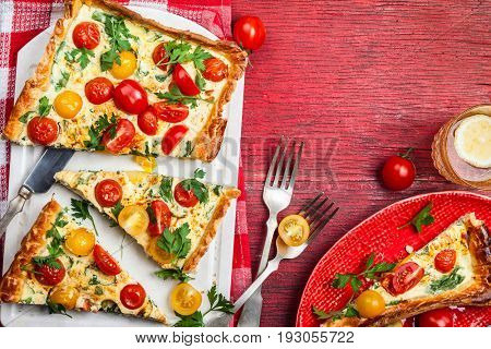 Deliciously simple tomato tart made with puff pastry, red and yellow cherry tomatoes, spinach and ricotta cheese. Concept of healthy eating or vegetarian food on  rustic wooden background, top view.