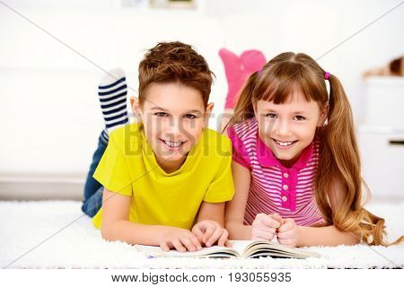 Two happy kids spending time at home, reading a book. Free time, activity and hobby. Education. Family at home.