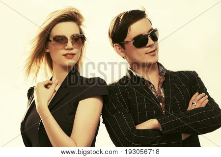 Happy young fashion couple walking in city street. Stylish trendy model in sunglasses outdoor