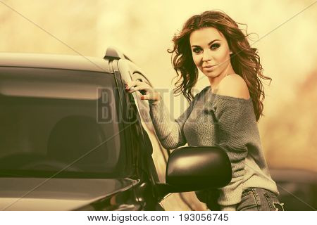 Young fashion woman in pullover standing next to her car. Stylish female model with long curly hairs outdoor