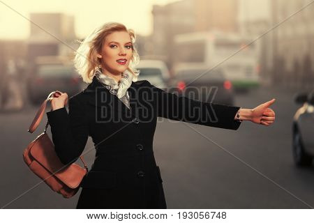 Happy fashion blond woman with handbag hailing a taxi cab walking in city street. Stylish female model in black coat outdoor