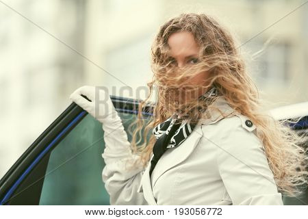Sad beautiful fashion woman with long curly hairs standing beside a her car