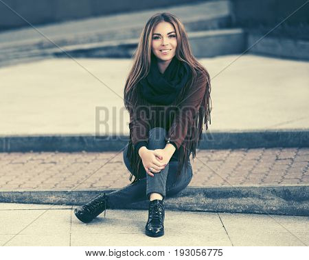 Happy young fashion woman sitting on city sidewalk. Stylish female model in leather fringe suede jacket and blue jeans