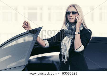 Fashion business woman talking on cell phone beside a car. Stylish female model in sunglasses outdoor