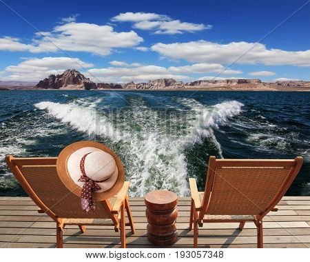 Waves from the boat cut through the Lake Powell on the Colorado River. At the stern of the vessel are two deck chairs. On the back of one hanging elegant ladies straw hat