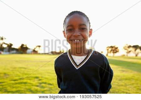 Portrait of African elementary school girl smiling in a park