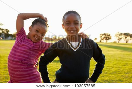 Two African elementary schoolgirls pose to camera in a field