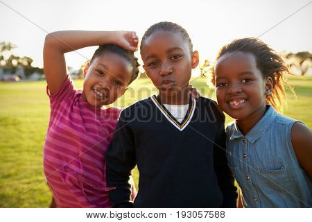 Three African elementary schoolgirls pose to camera in field