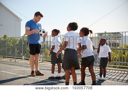 Young kids in a school playground with teacher holding ball