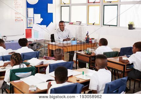 Teacher and kids sitting at desks in elementary classroom