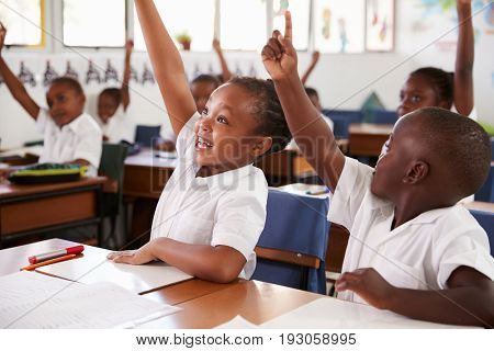 Kids raising hands during elementary school lesson, close up