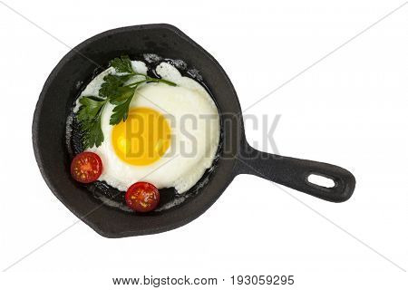 Black cast iron frying pan with fried egg isolated on white background, from above