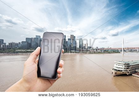 mobile phone with modern buildings by river in chongqing