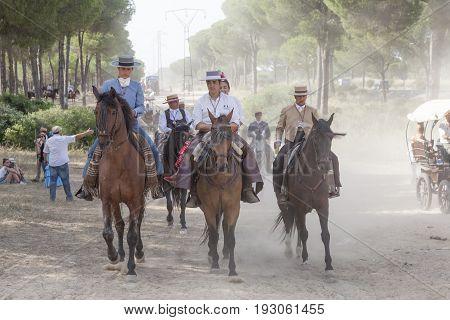 El Rocio Spain - June 1 2017: Pilgrims on horseback in traditional spanish dress on the road to El Rocio during the Romeria 2017. Province of Huelva Almonte Andalusia Spain