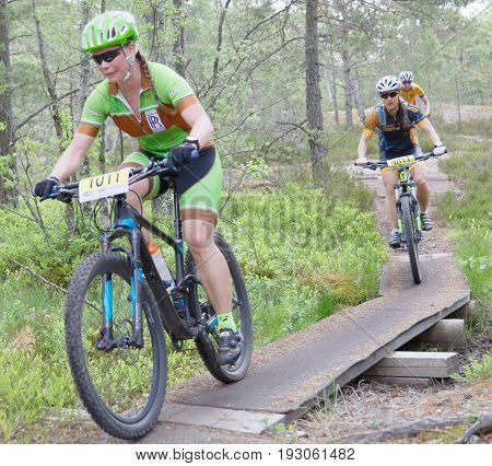 STOCKHOLM SWEDEN - JUNE 11 2017: Female mountain bike cyclist in the forest cycling over a bridge in the forest at Lida Loop Mountain bike Race. June 11 2017 in Stockholm Sweden