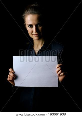 Coming out into the light. Portrait of woman in the dark dress isolated on black background showing blank paper sheet