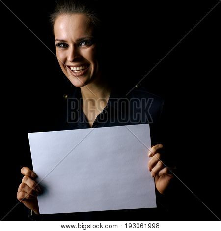 Сoming out into the light. Portrait of smiling woman in the dark dress isolated on black background showing blank paper sheet