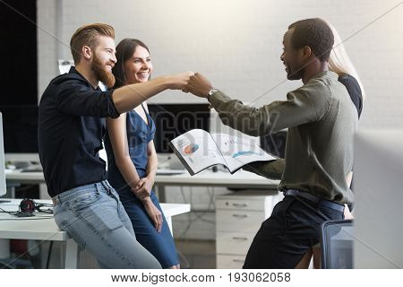 Group of happy young business people celebrating success with a fist bump in an office