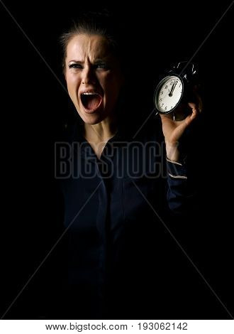 Coming out into the light. Portrait of stressed woman in the dark dress isolated on black background with alarm clock