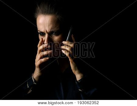 Coming out into the light. Portrait of stressed woman in the dark dress isolated on black background speaking on a smartphone