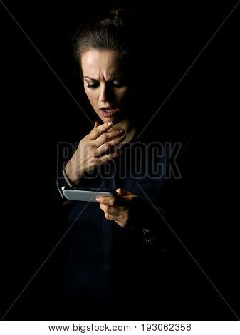 Сoming out into the light. Portrait of stressed woman in the dark dress isolated on black reading sms
