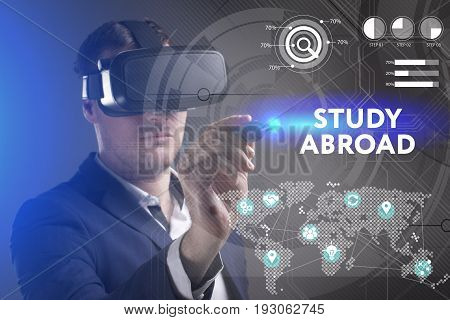Business Technology Internet and network concept. Young businessman working in virtual reality glasses sees the inscription: Study abroad