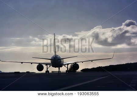 Silhouette of a big passenger airplane at a runway  Silhouette of a passenger airplane making a touchdown in a runway at an airport at dusk