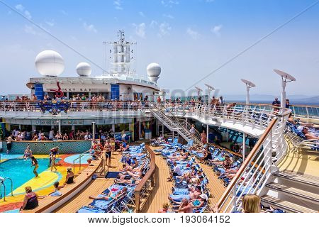 Mediterranean Sea - June 17 2016: Passengers aboard Royal Caribbean's Brillance of the Seas relaxing by the pool during a day at sea.