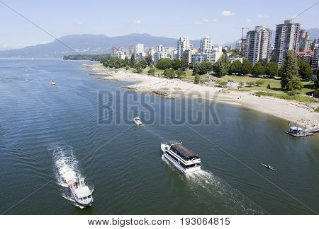 The view of busy False Creek water traffic and Sunset Beach park with Vancouver downtown skyline in a background (British Columbia).