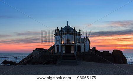 Chapel Senhor da Pedra on Miramar Beach at night, Porto, Portugal.