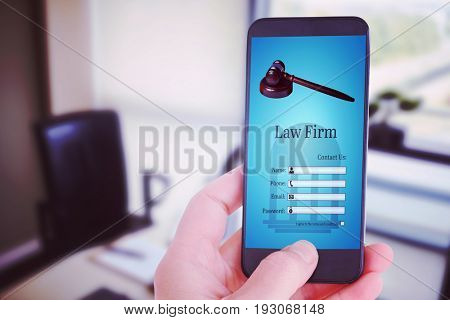 Female hand holding a smartphone against chair and desk in office