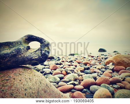 Bizzare Rock On The Pebbles Beach, Dramatic Sky Above. Stony  Offshore.
