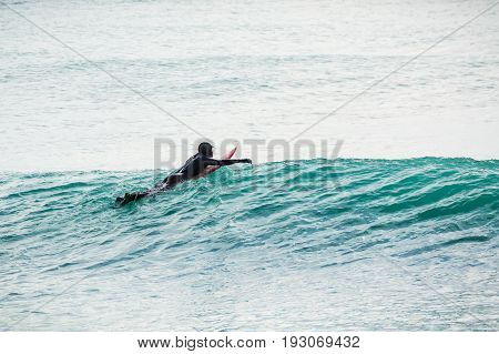 Surfer on turquoise wave in ocean. Surfer on wave
