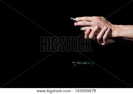 Addiction. Cigarette addict holding cigarette in his hands. Ashtray. Dark image. Black background. Smoking cigarette. Ashtray.