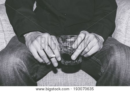 Man holding a glass of whiskey and smoking a cigarette. Black and white. Addiction concept.