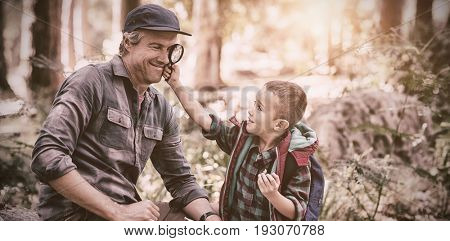 Curious little boy showing magnifying glass to father while hiking in forest