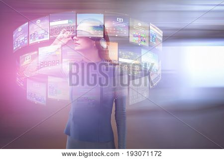 Woman experiencing virtual reality headset against view of office corridor and workspace