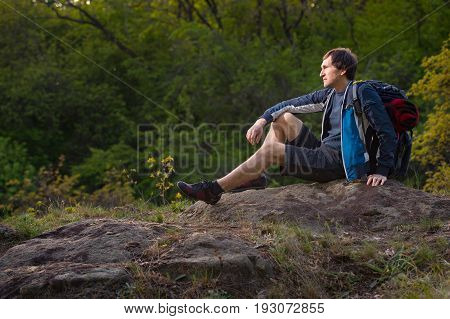 Hiker man takes a rest during summers expedition. Travel vacation holidays and adventure concept.