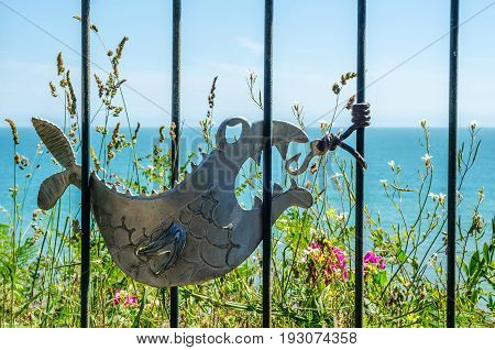 Metal Ornament On A Balustrade In A Seaside Village, Symbolic In The Shape Of A Fish, Ocean And Plai