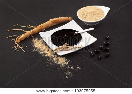 Healthy Ginseng supplements. Fresh root pills extract and powder on black background.